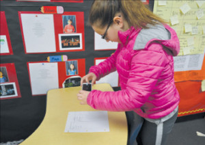 Bullis Charter School fifth-grader Anna Morokutti takes a photo of a document to upload to her FreshGrade account.